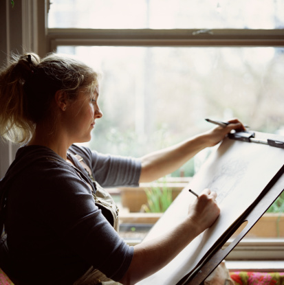 88165357-woman-drawing-on-easel-gettyimages